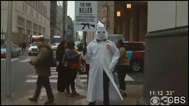 African American dresses in KKK hood on Philadelphia street corner